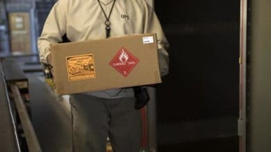 Warehouse worker holding box with a hazmat label on it