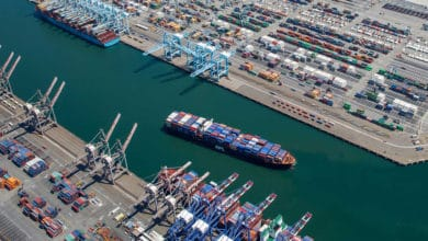 A photograph of a container vessel sailing into a shipping channel at a port. There are cranes at the dock and hundreds of container boxes sitting on land.