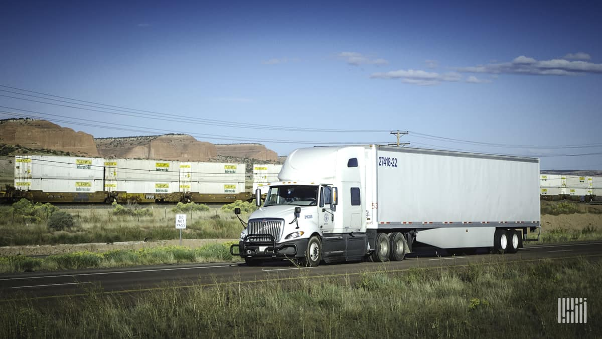 White truck with double-stack intermodal train in background