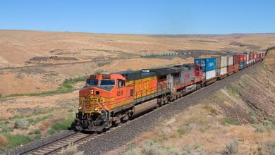 A photograph of a train pulling intermodal containers across a field.