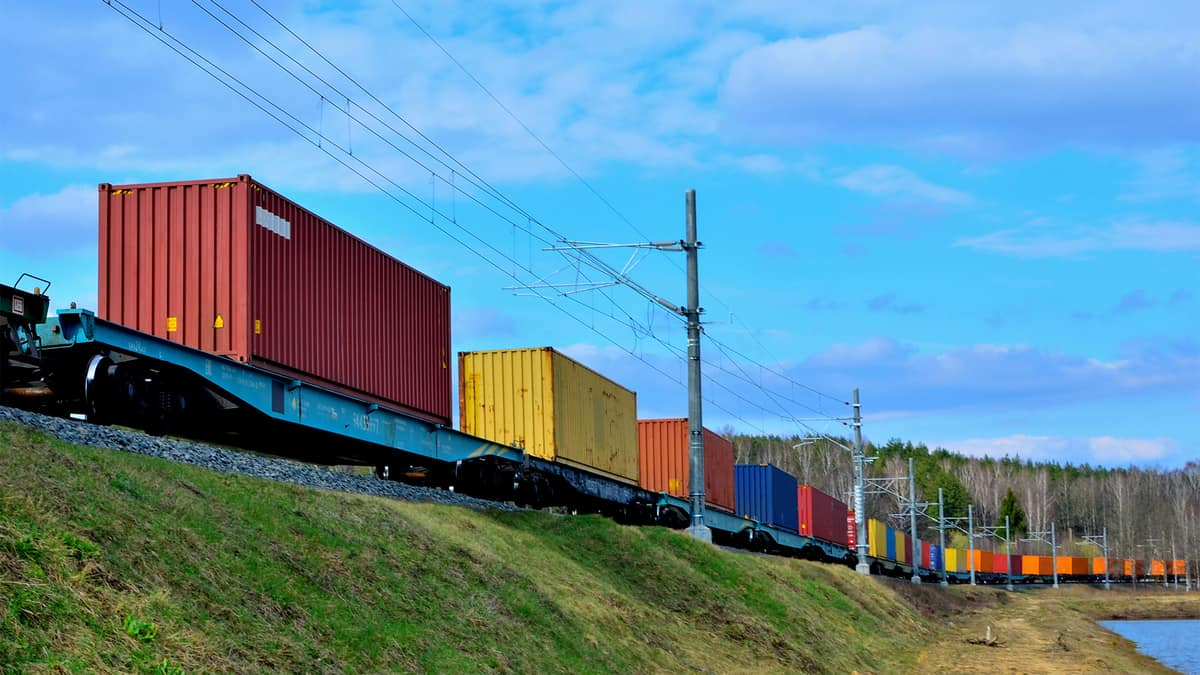 A photograph of intermodal containers on railway track that's on a hill.