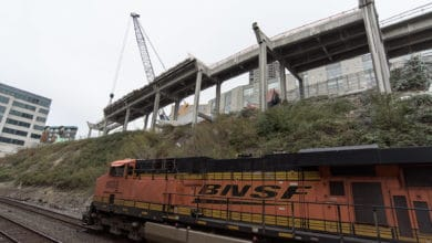 A photograph of a train locomotive traveling next to a construction site.