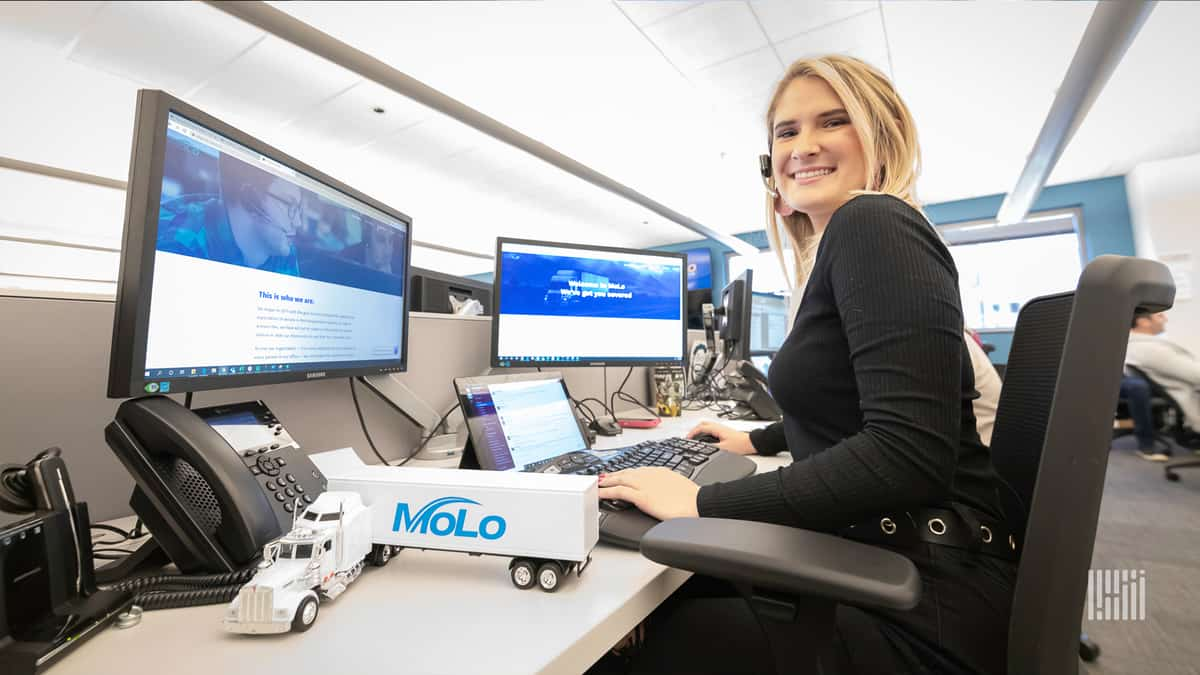 Young woman with headset at her Molo Solutions work station.