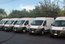 White delivery vans parked in a lot.