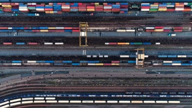 A photograph of an aerial view of a rail yard. There are rows of intermodal containers and railway track.