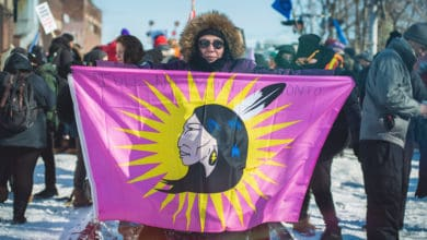 A photograph of a person holding a flag with the image of a First Nation person on it. There is a crowd of people behind the person.
