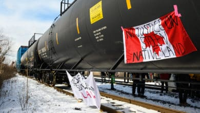 "A photograph of tank cars on a rail track. One of the tank cars has a Canadian flag hanging from it. Written on the flag are the words, ""no justice on stolen native land."""