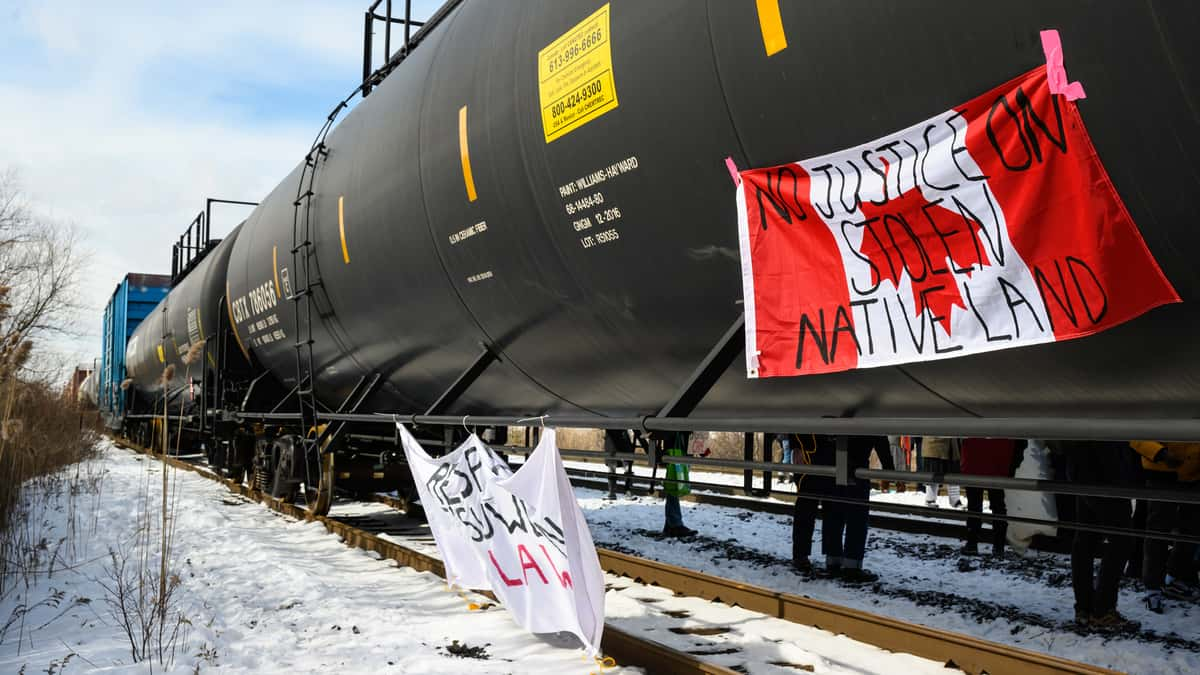 """A photograph of tank cars on a rail track. One of the tank cars has a Canadian flag hanging from it. Written on the flag are the words, """"no justice on stolen native land."""""""