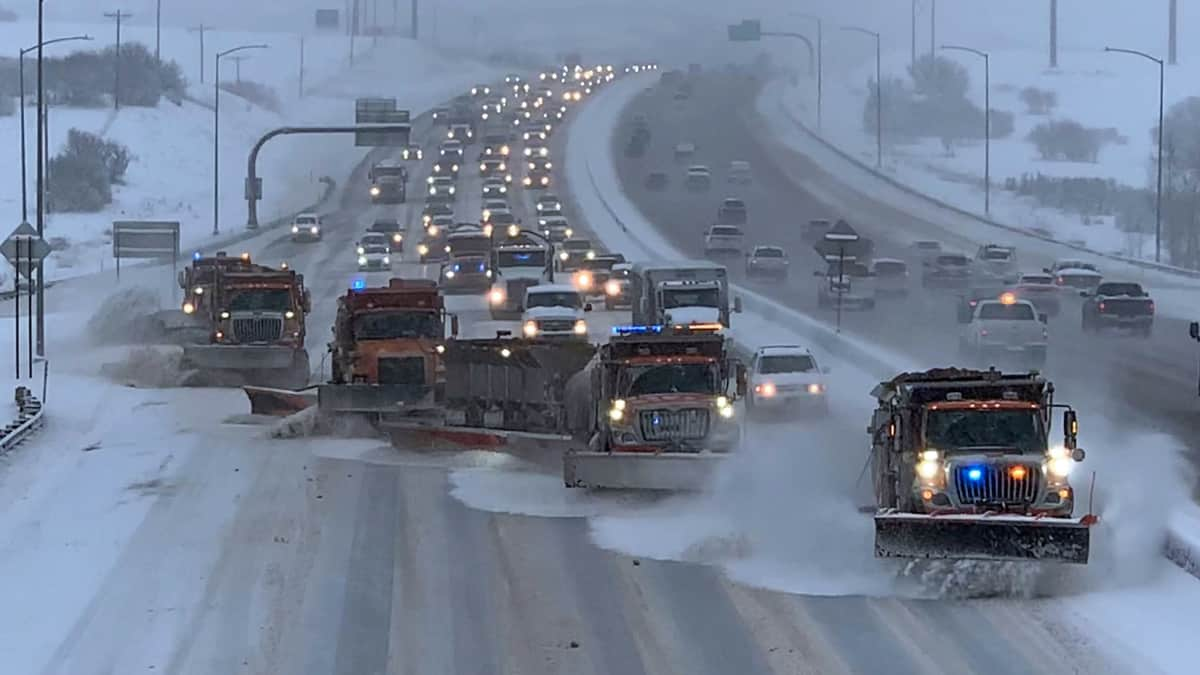 Plows clearing a snowy Colorado highway.