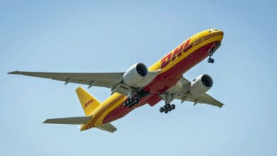Mustard yellow DHL plane flying overhead.