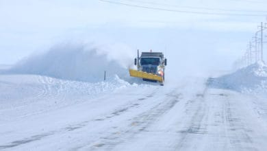 Plow clearing very snowy road in Idaho.