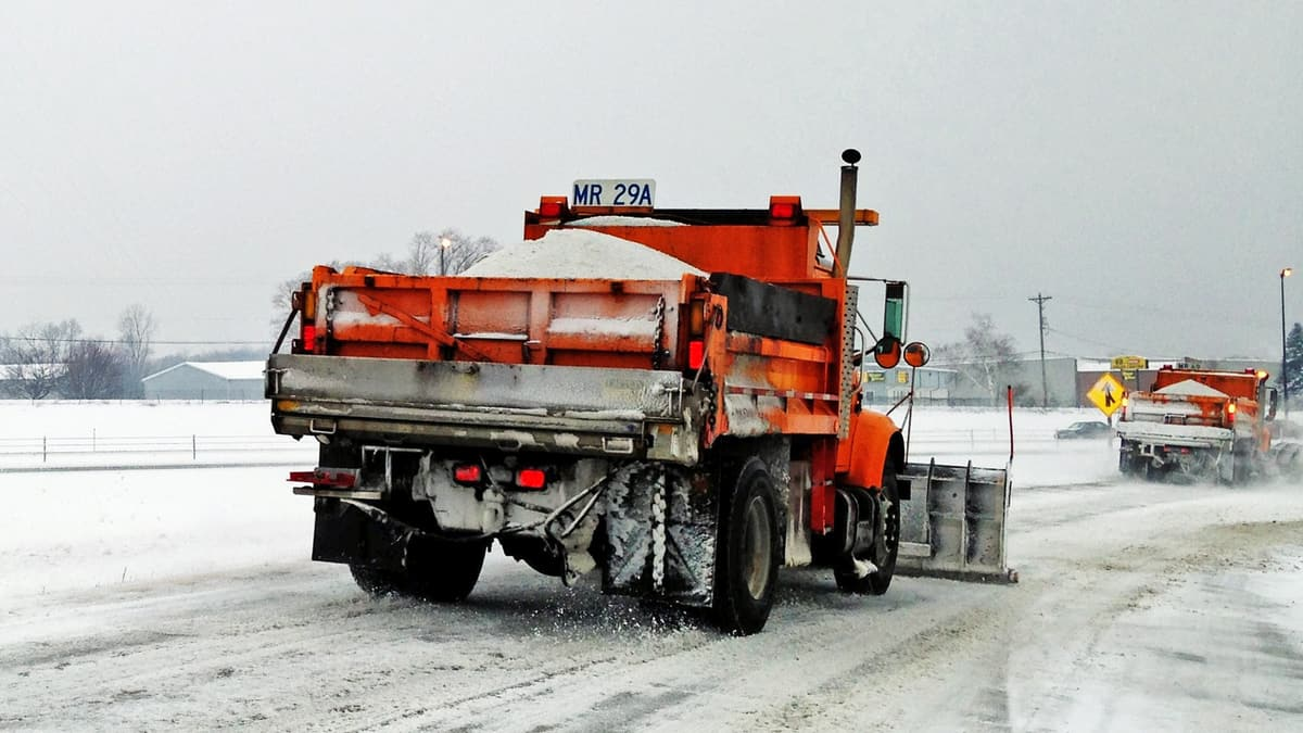 Plows clearing snowy Illinois highway.