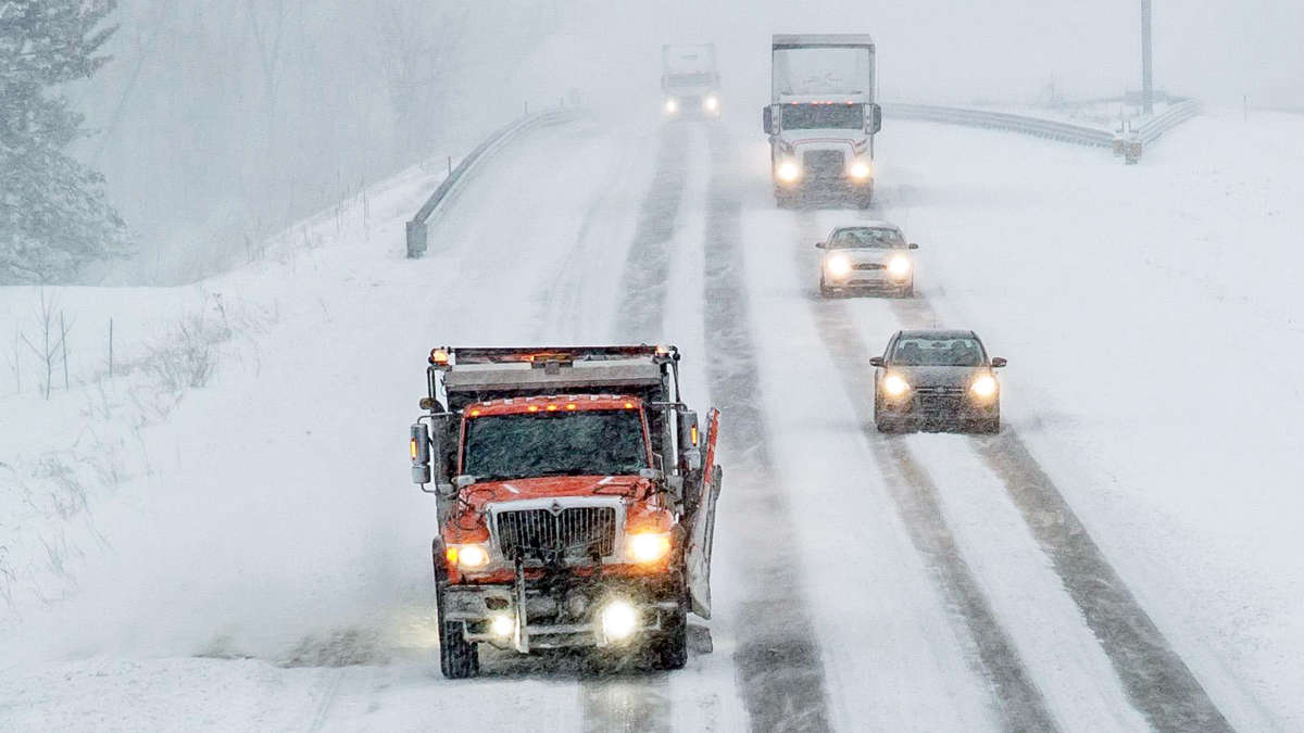 Plow clearing snowy Michigan road, with cars and a tractor-trailer behind it.