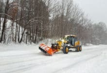 Plow clearing snowy New Hampshire road.