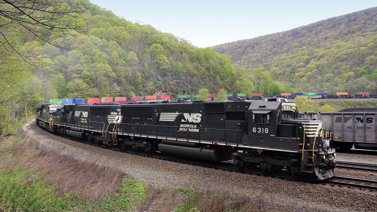 A photograph of a train locomotive hauling intermodal containers by two hillsides.