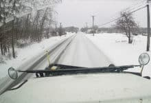 Plow clearing snowy Ohio road.