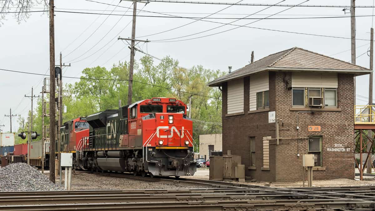 A photograph of a train next to a building.