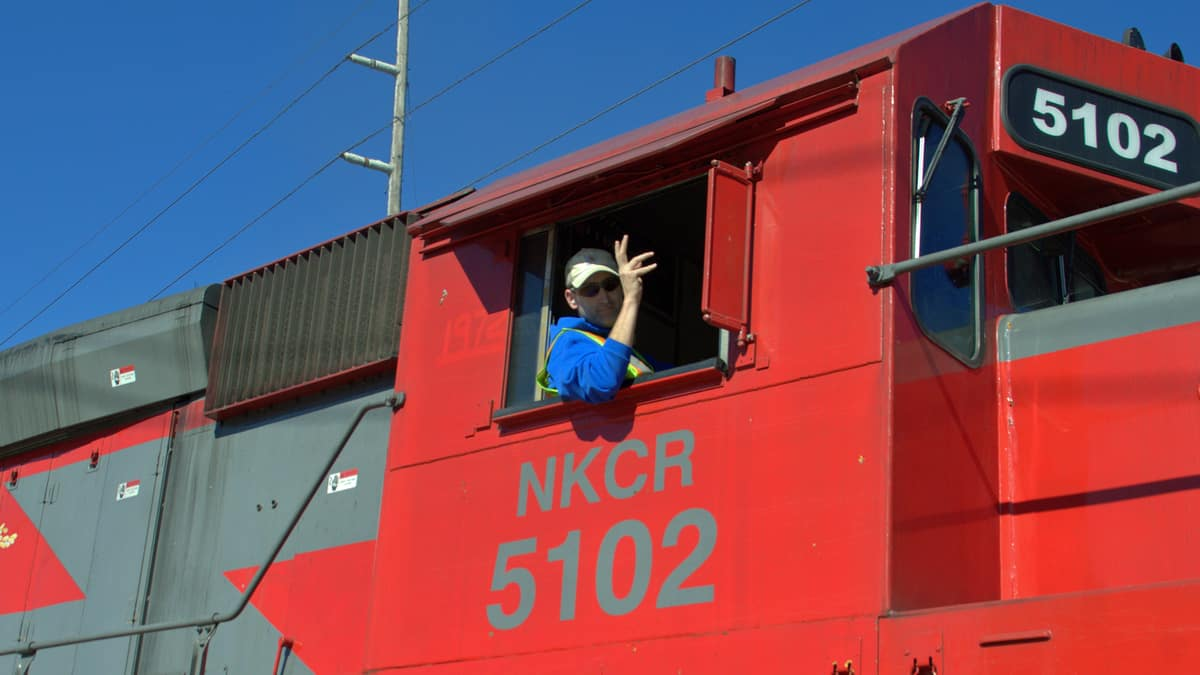 A photograph of a man leaning out of the window of a train.