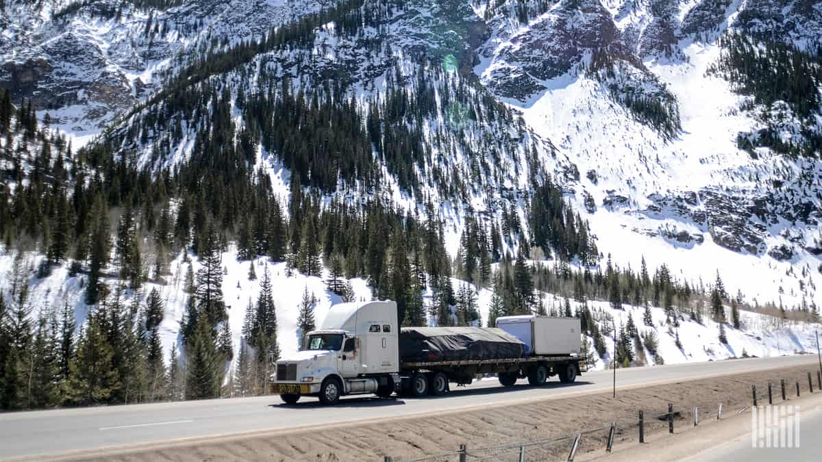 Tractor-trailer on mountain road with snow in background.