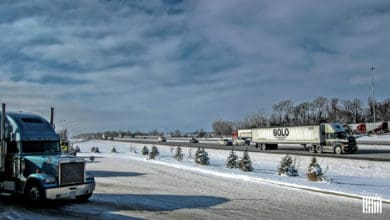 Tractor-trailers heading down a snowy road.