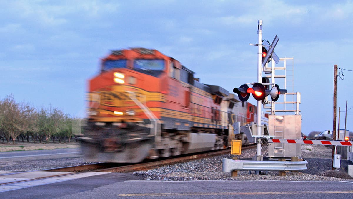 A photograph of a train at grade crossing.