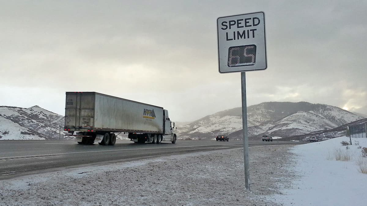 Tractor-trailer on Utah highway surrounded by snow-capped mountains.