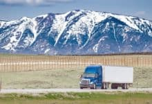 unidentified tractor-trailer on highway with snowy mountains in backdrop