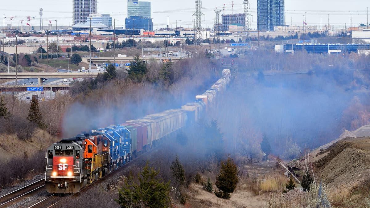 A photograph of a train traveling through a wooded area. There are city buildings on the horizon.