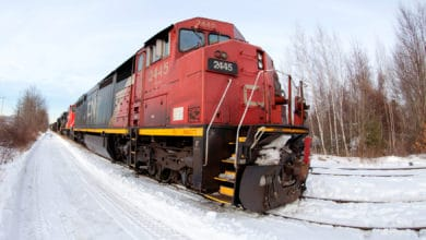 A photograph of a train. There is snow on the ground and bare trees next to the train.