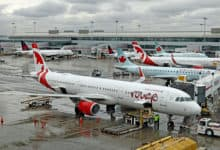 Air Canada planes at the airport gate on a rainy day.