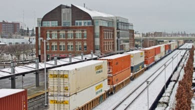 A photograph of a train hauling intermodal containers traveling through a downtown area in wintertime.
