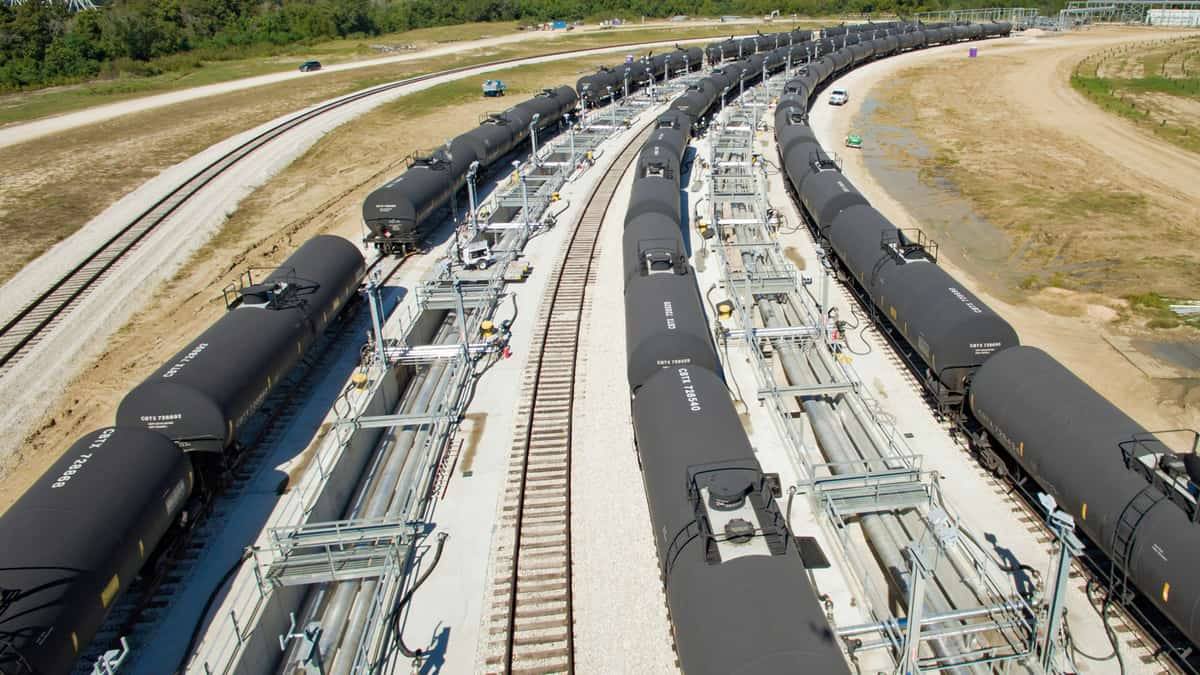 A photograph of three long lines of tank cars sitting at a rail yard.