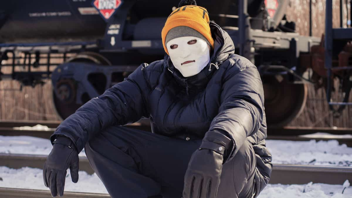 A photograph of a man with a mask on his face. He is sitting next to a train.