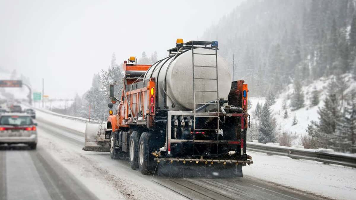 Plows clearing snowy Colorado highway.