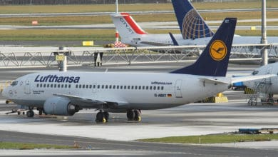 Lufthansa plane on taxiway at airport.