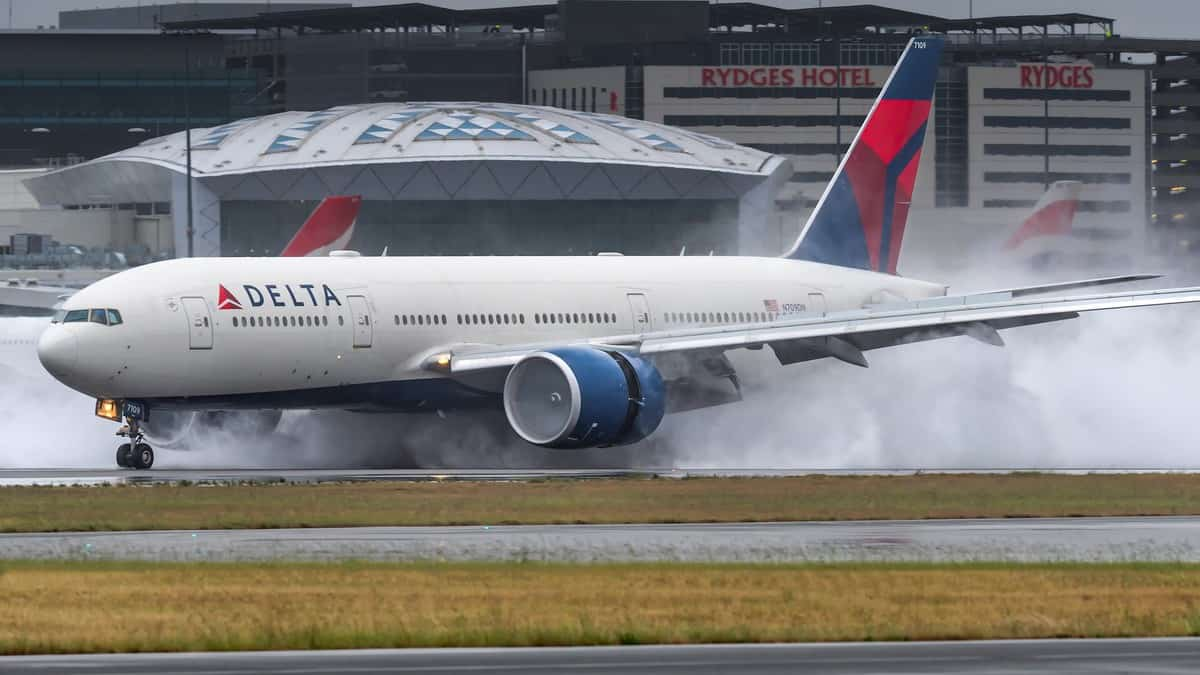 Smoke comes from wheels as big jet touches down on runway.