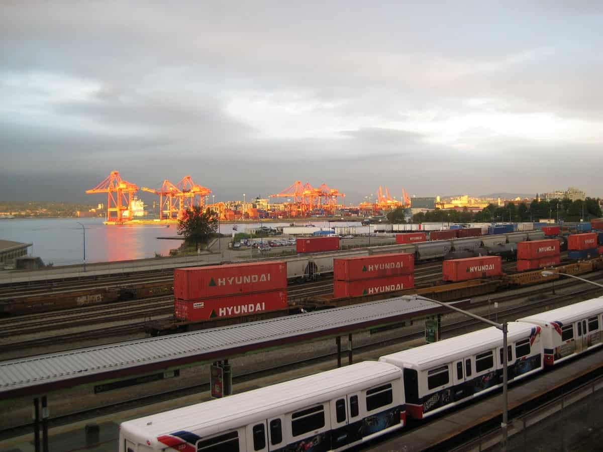 A photograph of a rail yard. There are intermodal containers and rail cars There are loading cranes at a port in the background.