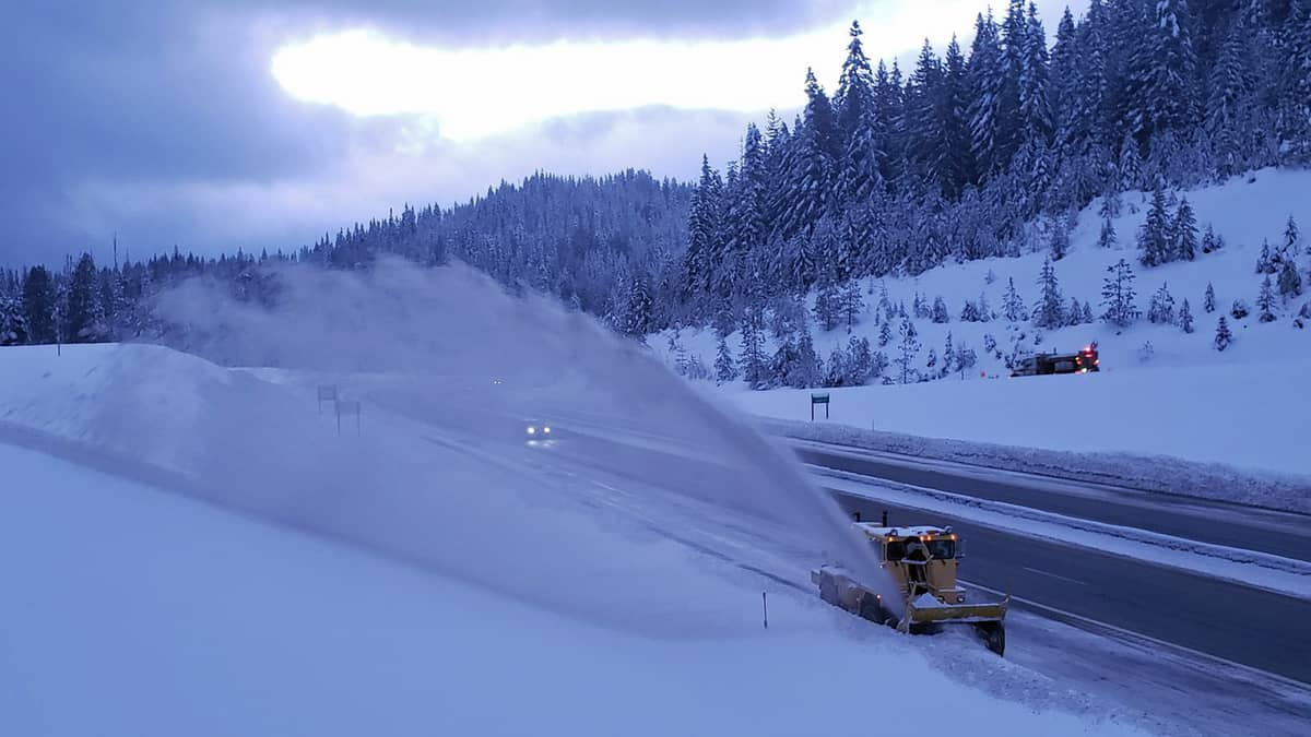 Plow clearing snowy highway in Idaho.