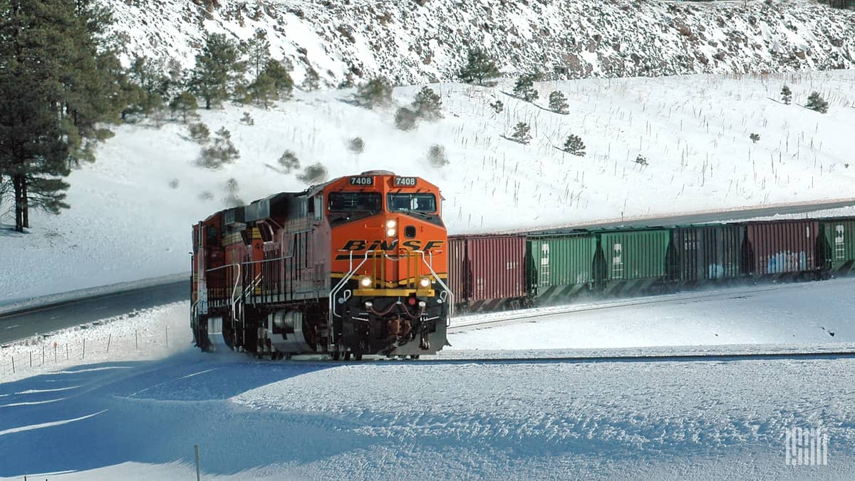 Freight train moving through a snow-covered landscape.