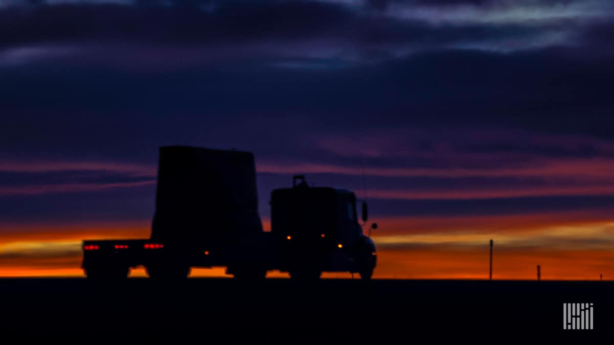 Flatbed truck on highway at sunset.