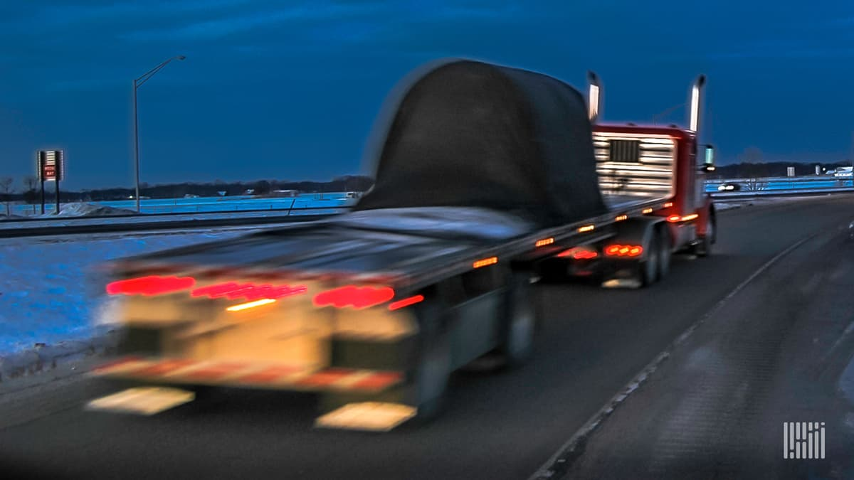 Flatbed truck on highway at night.