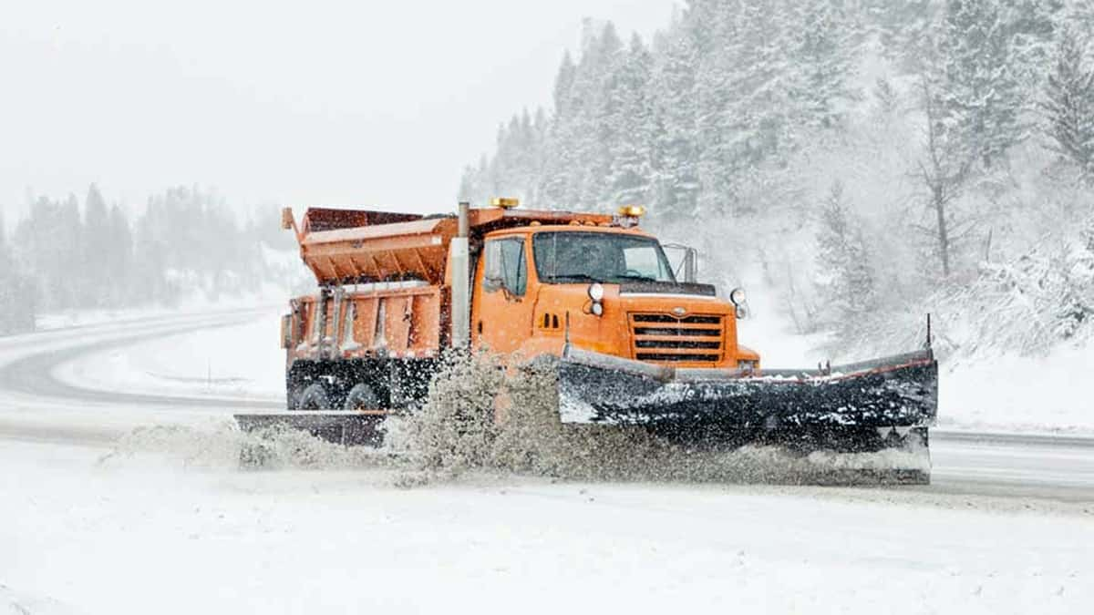 Plow clearing snowy highway in Montana.