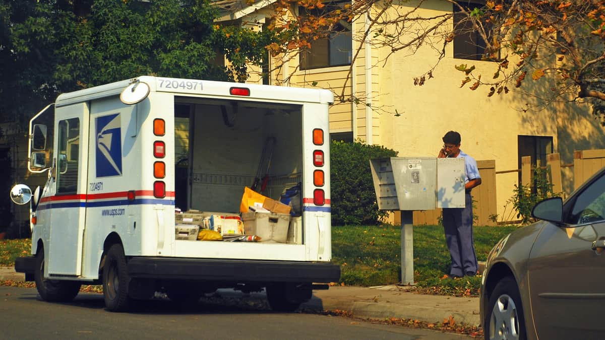 USPS truck and mailman delivering mail.