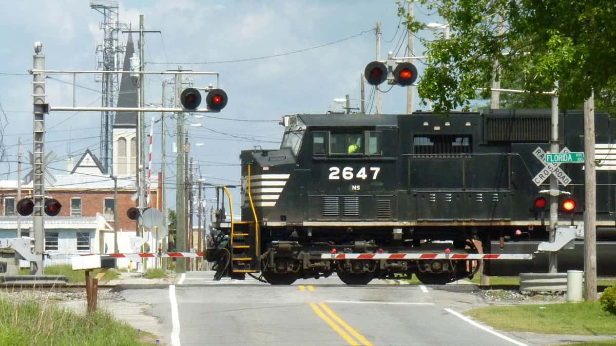 A photograph of a train on railroad tracks crossing a town road. There are signs and signals around the train for drivers and pedestrians.