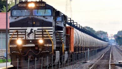 A photograph of a train nearing a rail yard.