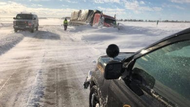 Flatbed truck stuck on side of snowy North Dakota road.