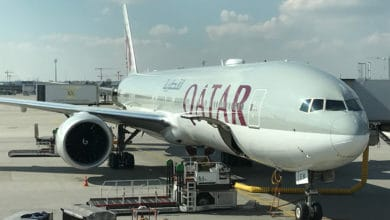 Large, gray Qatar Airways at airport gate.
