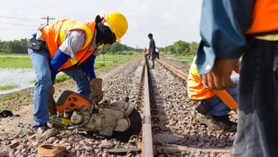 A photograph of two workers fixing a railroad track. A third person is standing on the railroad track in the distance.