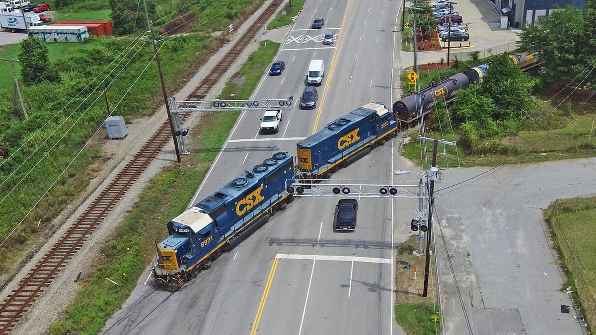An aerial photograph of a train driving through a road. Vehicles on either side of the train are waiting for the train to pass by.