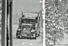 Tractor-trailer on a very snowy highway.